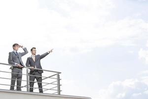 Businessman showing something to coworker against cloudy sky