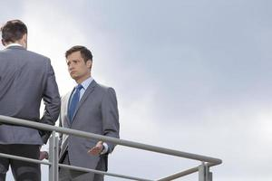 Serious businessman looking at coworker against clear sky photo