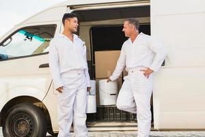Painters smiling leaning against their van