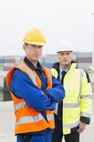 Portrait of confident worker standing with coworker in shipping yard photo