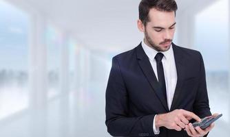 Imagen compuesta de empresario concentrado en traje usando calculadora