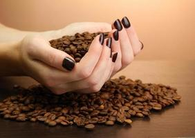 Manos femeninas con granos de café, sobre fondo marrón