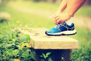 tying shoelace on stone bench in green grass photo