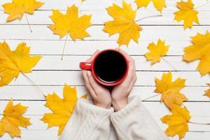 mãos femininas segurando uma xícara de café na mesa de madeira.