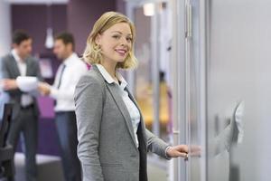 Pretty blond businesswoman open de door office. Concept
