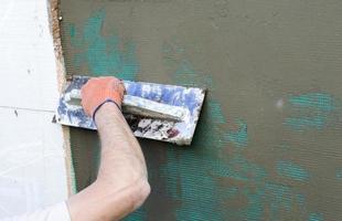aplicando masilla a la pared usando una espátula foto