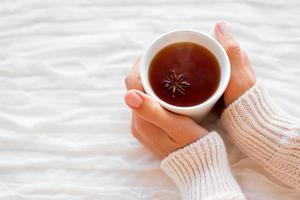 Women holds a cup of hot tea with anise star.