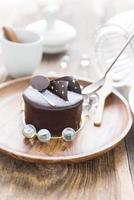 Pastel de chocolate negro sobre fondo de madera