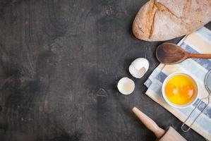 Baking background with eggshell, bread, flour, rolling pin photo