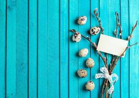 Quail eggs and willow branch on a wooden background photo