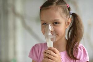 encantadora niña con inhalador foto