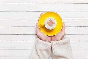 mains féminines tenant une tasse de café sur la table en bois.