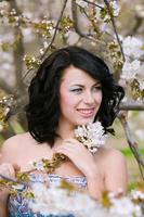 Young beautiful girl in spring blooming garden photo