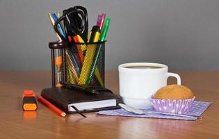 suministros de oficina, taza de café y pastel