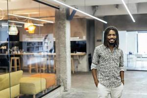 Handsome black worker standing in office