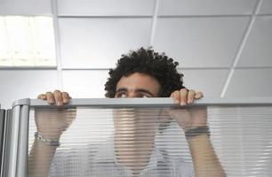 oficinista mirando por encima de la pared del cubículo