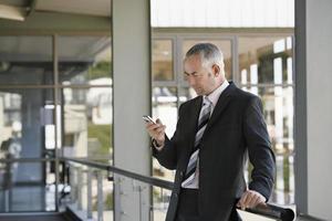 zakenman die mobiele telefoon in bureau met behulp van
