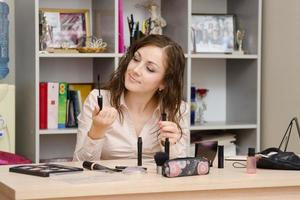 Girl in the office chooses cosmetic mascara