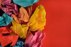 Grupo colorido de bolas de papel sobre fondo de papel rojo.