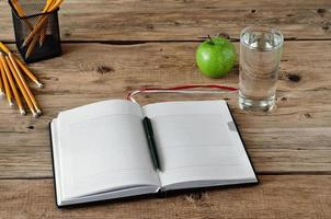 Open diary with blank pages with a glass of water photo