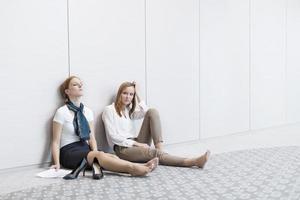donne di affari frustrate che si siedono sul pavimento in ufficio