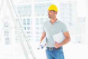 Handyman with blueprints and clipboard in office photo