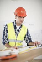 capataz en su oficina revisando planes de construcción foto