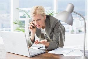 empresaria en el teléfono y usando su computadora portátil foto