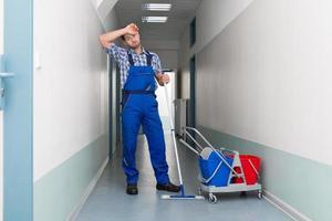 Trabajador de sexo masculino cansado limpieza pasillo de la oficina foto