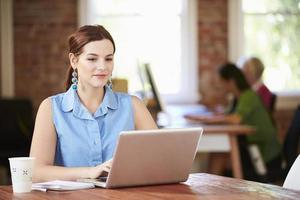 Mujer que trabaja en la computadora portátil en la oficina contemporánea