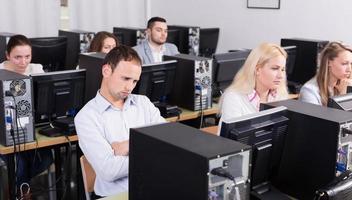 personal sentado en escritorios y mirando pantallas de pc foto
