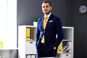 Handsome businessman in suit looking at camera in office