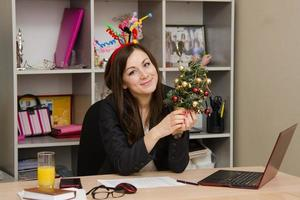 Girl in the office with a Christmas tree
