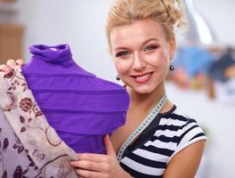 Diseñador de moda sonriente parado cerca del maniquí en la oficina
