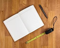 Bloc de notas en blanco con material de oficina en mesa de madera.