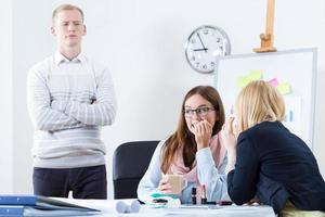 Two girls gossiping in the office with man looking over photo