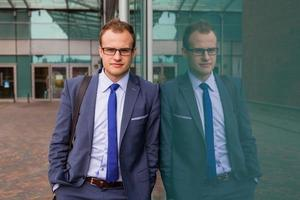 Portrait of young businessman standing in front of office block.