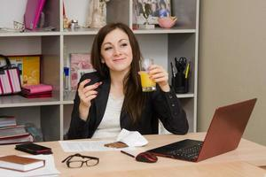 Girl in office holding a glass of juice and chocolate