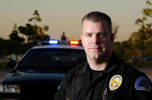 colpo di testa di sera del poliziotto maschio con auto dietro