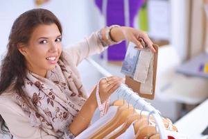 hermosa joven estilista cerca de estante con perchas foto