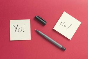 Yes no paper notes post on a red background