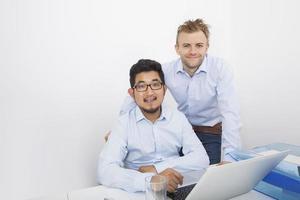 Retrato de empresarios con laptop en el escritorio en la oficina foto