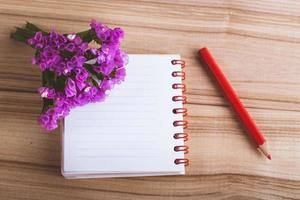 flowers notebook and pencil on wooden background photo