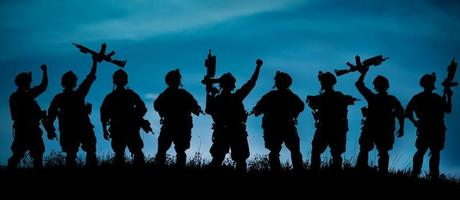 Silhouette of military soldiers team or officer with weapons at
