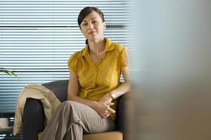 Businesswoman in yellow short-sleeved blouse sitting in office c