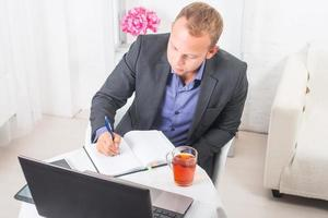 Businessman in office sitting at  table with a laptop writes photo