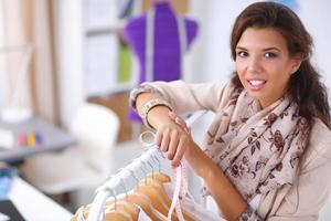 Beautiful young stylist woman near rack with hangers