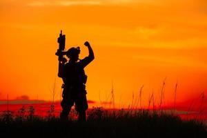 silueta de soldado militar u oficial con armas al atardecer