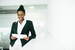 una mujer joven sonriendo y sosteniendo un papel en la oficina