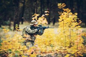 soldado con rifle en el bosque